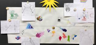 Koulun oppilaiden STEAM-aiheisia taideteoksia seinällä.