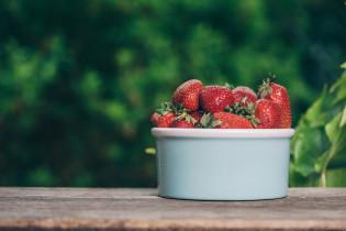 Kuvassa kulhollinen mansikoita pöydällä.
