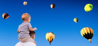 Mies ja hänen hartioilaan istuva pieni poika katsovat taivaalla lentäviä kuumailmapalloja
