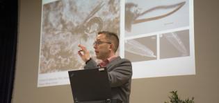 Professori Ilari E. Sääksjärvi luennoi taustallaan kuva hyönteisestä