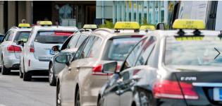 Monta taksia odottaa asiakkaita taksitolpalla