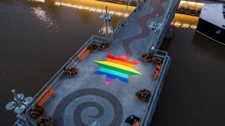 Teatterisillan tähti sateenkaaren väreissä ylhäältä kuvattuna ja sillan sivuilla näkyy Aurajokea. Kuva on otettu aamuhämärässä.