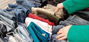 Naisen kädet valitsevat poistotekstiiliä myyntikorista