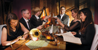 TFOn muusikoita pöydän ääressä taittelemassa joutsenia
