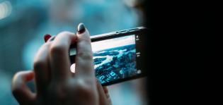 Nainen ottaa kuvan merenlahdesta puhelimellaan.