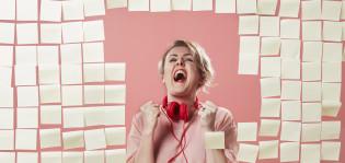 Nainen on liimannut post it -lappuja edessään olevan ikkunan lähes täyteen. Hänellä on punaiset kuulokkeet kaulallaan ja hänen ilmeensä kertoo, että jotain mahtavaa on tapahtunut.