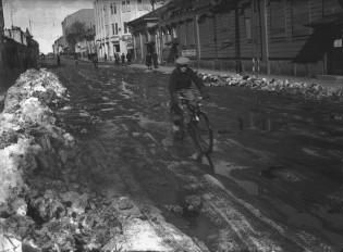 Pyöräilijä ajaa loskaisella kadulla
