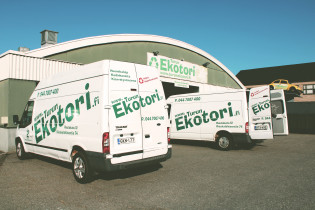 Ekotorin rekkoja on parkeerattu Ekotorin eteen. Rekat ovat valkoisia ja niissä lukee vihreällä tekstillä Ekotori.