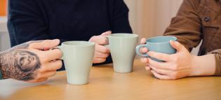 Kolme kahvinjuojaa pöydän ympärillä.
