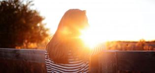 Tyttö nojaa kaiteeseen auringonlaskussa.