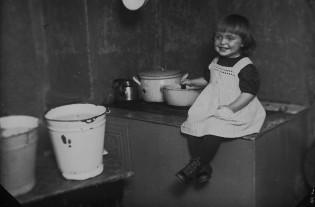 Pikkutyttö hellan reunalla. Kuvaaja: Turun Kuvaus. 1900-luvun alku