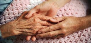 Vanhuksen kädet, joita pitelee nuoremman ihmisen kädet.