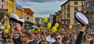 Taidemuseon mäki on täynnä vapun juhlijoita, ihmiset heiluttavat ylioppilaslakkeja ja taustalla näkyy paljon keltaisia ilmapalloja.