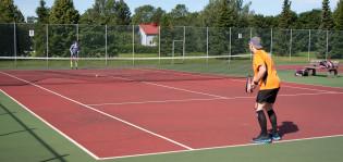 Kaksi henkilöä pelaa tennistä.