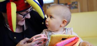 vauva ja hassuhattuinen täti leikkimässä
