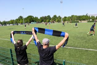 Kaksi jalkapallokannattajaa kannustaa ottelua kentän reunalla. He heiluttavat korkealla ilmassa fanihuiveja.
