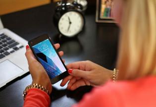 Kuvassa nainen käyttää älypuhelinta, taustalla tietokone
