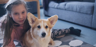 Tyttö ja koira ovat lattialla ja katsovat kameraan