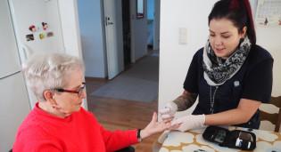 Naistyöntekijä mittaa kotihoidon naisasiaakkaalta verensokerin ruokapöydän ääressä.