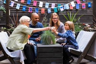 Perhe juhlii yhdessä puutarhassa SUomi 100 -lippujen alla