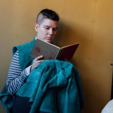 Henkilö nojaa seinää vasten ja lukee kirjaa.