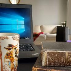 Työpöytä, jonka päällä tietokone, kahvimuki ja vanhoja kirjoja.