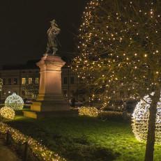 Per Brahen patsas, jossa 1600-luvun asuun pukeutunut seisova mieshenkilö. Taustalla pyöreät valokehät, jouluvalot Brahenpuiston vihreällä nurmikolla