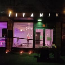 Rakennus, jonka ikkunasta näkyy sisään galleriaan. Titanik-valokirjaimet loistavat pimeässä sisäänkäynnin yläpuolella.