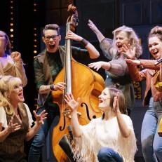Seitsemän naista laulamassa lavalla kontrabasson ympärillä