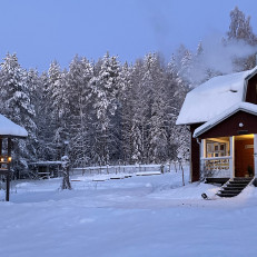 Mattilan tilan päärakennus ja aitta lumisessa talvimaisemassa, takana näkyy metsää.