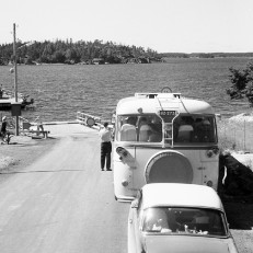 Vanha linja-auto odottaa vuoroaan linja-auton takana lossirannassa. Lossi on juuri saapumassa vastarannalta kyydissään henkilöauto ja kaksi kuorma-autoa.