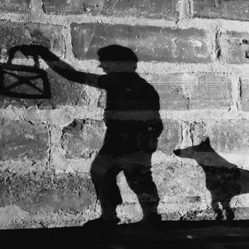 Varjokuva lapsesta lyhtykädessä koiran seurassa
