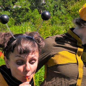 kaksi naista puhaltelevat taustalla vihreää puistikkoa