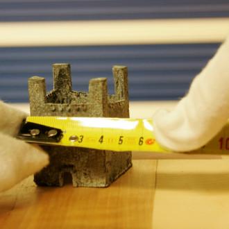 Taideteoksen mittaamista keltaisella rullamitalla, jota pitelevät valkoisiin puuvillahanskoihin verhotut kädet.