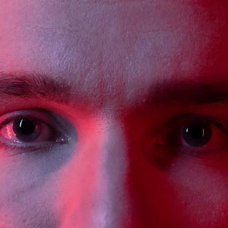 Nuoren miehen silmät lähikuvassa, punaisessa yökerhovalossa.