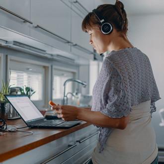 Digituen kuvituskuva, Digi- ja väestötietovirasto, nainen katsoo kannettavaa tietokonetta.