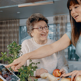 Digituen kuvituskuva, Digi- ja väestötietovirasto. Nainen antaa isoäidilleen digitukea keittiössä tabletilla.