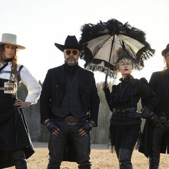 Forkin jäsenet pellolla, mustissa steampunk-henkisissä asuissa.