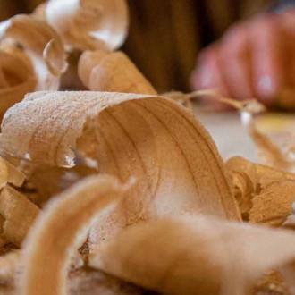 Ett handpar sysselsatt med träarbete