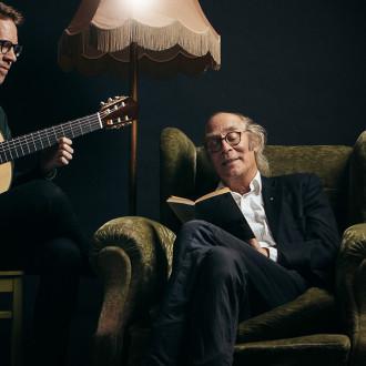 Vesa Vierikko nojatuolissa, vieressään kitaristi.