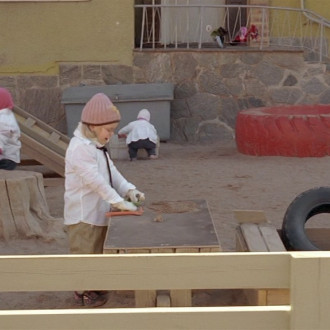 valkoisiin työtakkeihin pukeutuneita leikki-ikäisiä lapsia päiväkodin pihassa
