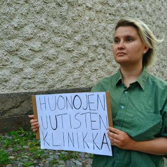 Kuvassa vaaleatukkainen nainen, jolla on käsissään kyltti jossa lukee Huonojen uutisten klinikka.