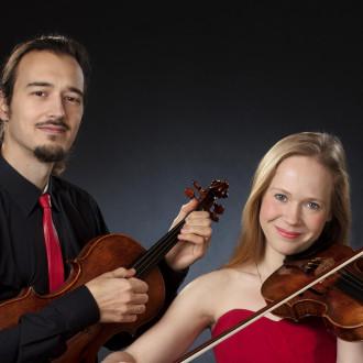 Kuvassa on kaksi ihmistä, joilla toisella on käsissään alttoviulu ja toisella viulu.