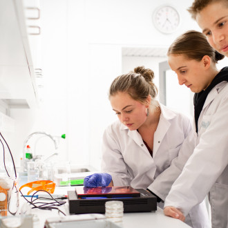 Ryhmä opiskelijoita (kaksi tyttöä ja poika) kumartuneena tutkimaan näytteitä laboratoriossa.
