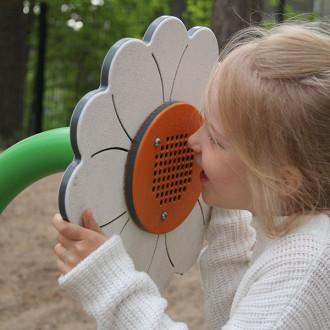Lapsi kuiskuttaa kukkaan.