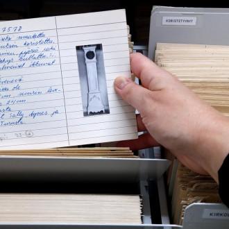Esinekokoelman pahvikortiston pahvikortissa on kuva esineestä, tässä tapauksessa kaappikellosta, ja pahvikorttiin on kirjattu sen tietoja mustekynällä.