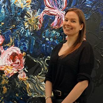 Blogin kirjoittaja seisoo ison maalauksen edessä. Maalauksessa voimakkaan värisiä kukkia (Heikki Marila).