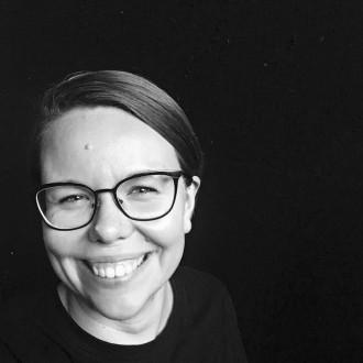 Kolmekymppinen, silmälasipäinen nainen hymyilee mustavalkokuvassa