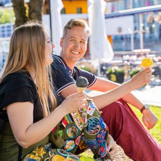 Nuori nainen ja nuori mies istuvat nurmikolla syömässä jäätelöä.