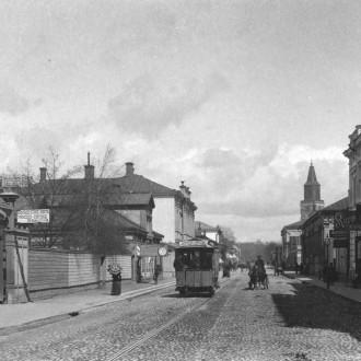 Puisia ja kivisiä kaupunkitaloja, kävelytiellä kulkee nainen päivänvarjon kanssa. Keskellä leveä katu, jolla hevosten vetämiä raitiovaunuja. Oikealla häämöttää Turun tuomiokirkko.